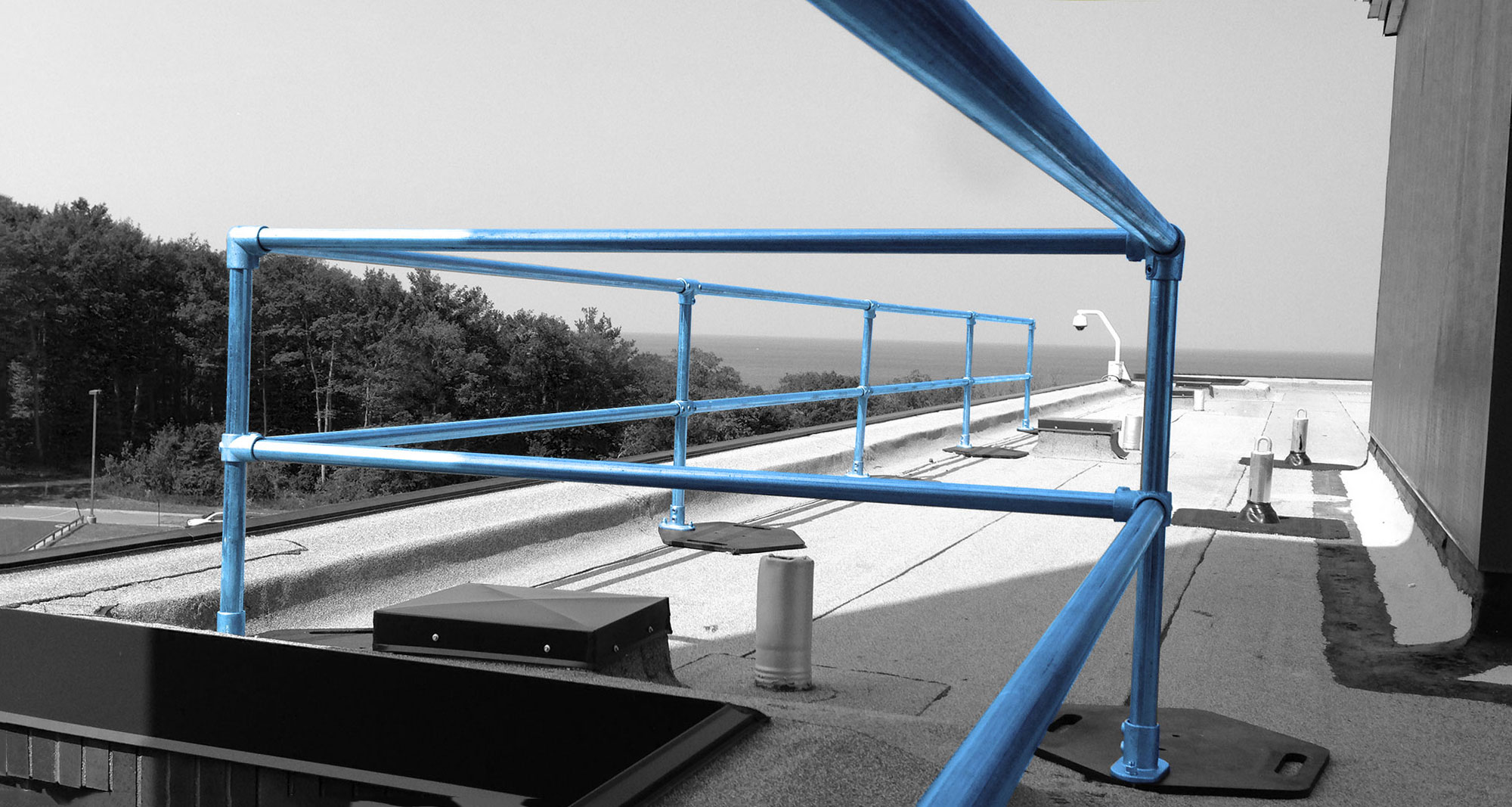 A blue guard rail on top of a warehouse. For more fall protection industry news, follow the Skyline FP blog.
