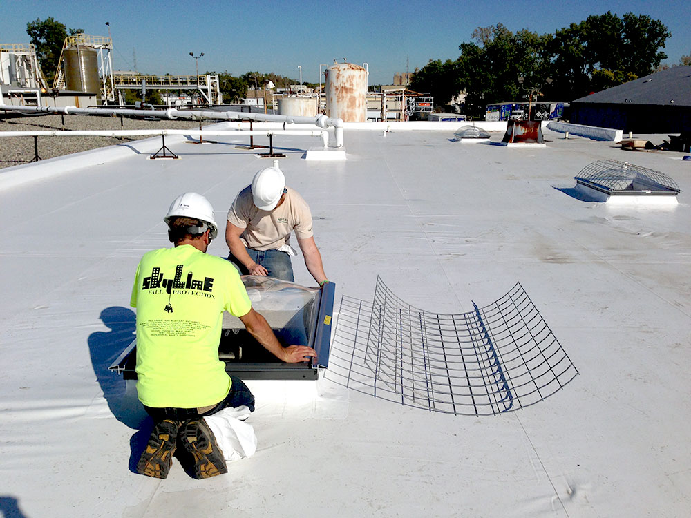 Skylight safety fall protection includes roof hatch access points. A crew covers a skylight with proper safety mesh