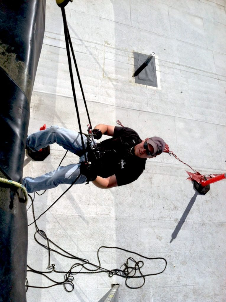 A Skyline technician conductiong fall protection equipment testing by hanging from a rooftop anchor while in a safety harness.