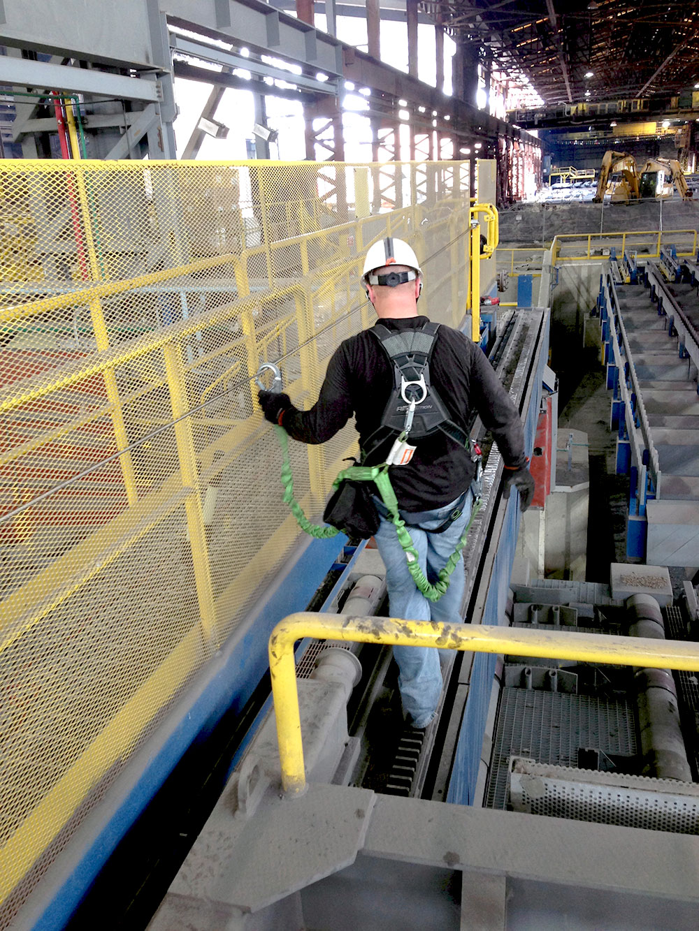 A Skyline fall protection inspection taking place as a technician walks a lifeline in a steel mill.