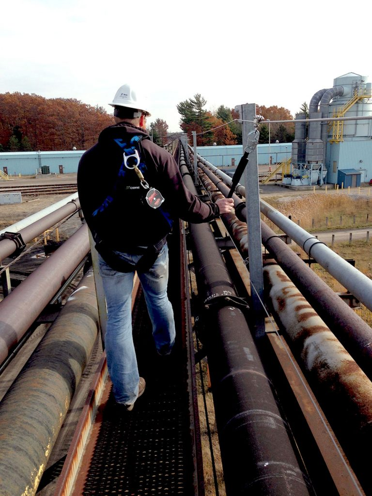A Skyline technician walks along a pipeline harnessed to a lifeline while conducting a fall protection risk assessment.