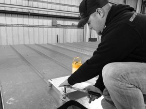 A Skyline Fall Protection member installing a rooftop anchor point. All part of proper OSHA fall protection compliancy.