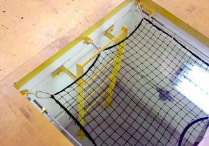 Fall arrest netting in place in an industrial workplace, covering a square hole that leads to a yellow ladder down the shaft..