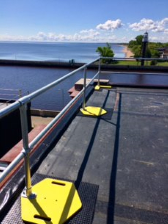 A handrail is set up along the edge of a 3-story building's rooftop. At what height is fall protection required? Anywhere there's a four-foot drop.