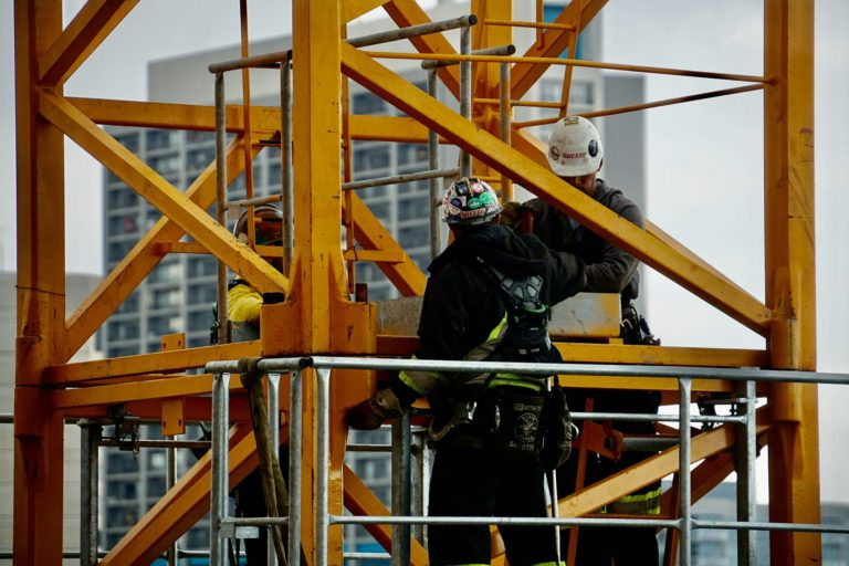 Skyline has the best fall protection standards in the industry. A harnessed crew operates on a building under completion.